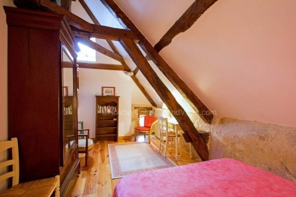 Le Moulin master bedroom with lovely oak beams
