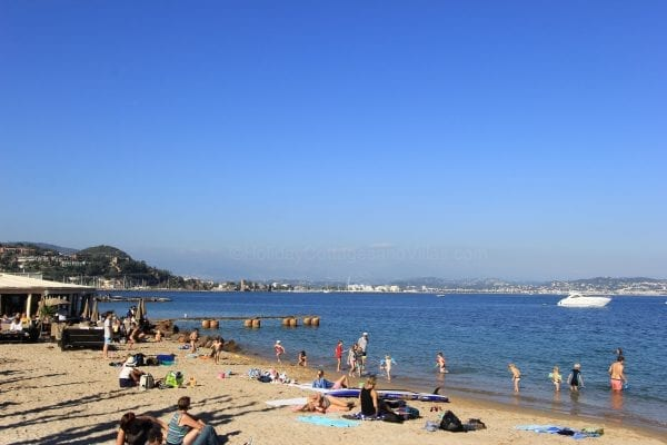 A beach looking over to cannes in the distance, the villa is up in the mountains in the far distance