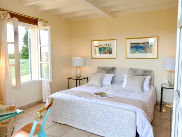 The master bedroom with double opening French doors onto the north facing terrace, the sun rises in the east through the window on the left