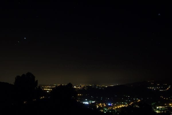 Night time view with cannes and antibes lit up in the distance, 2 cruise ships can be seen in the distance