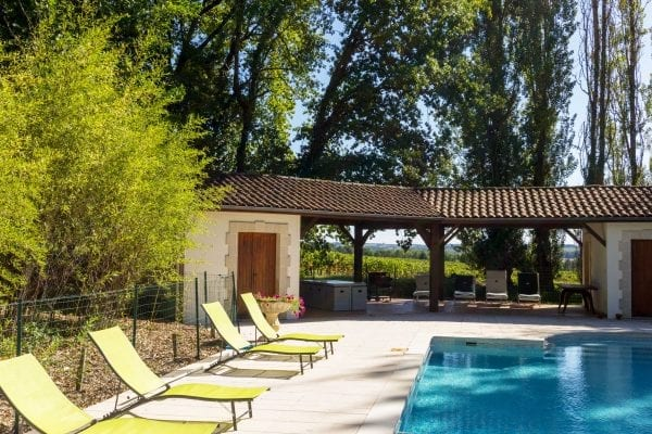Shaded seating by the pool, loungers and a table, vineyard views